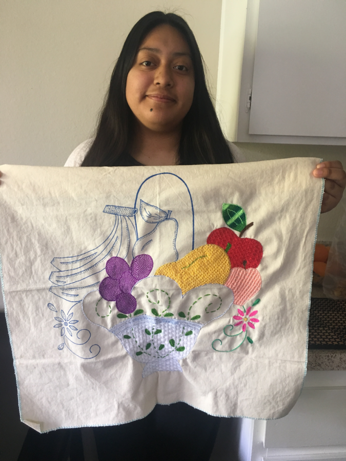 Dafne Calderon, Class of 2020, shows off the embroidery she made during quarantine in her ceramics class.